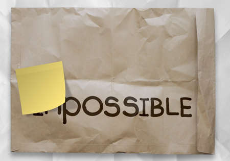 transformed: sticky note over word impossible transformed into possible as concept