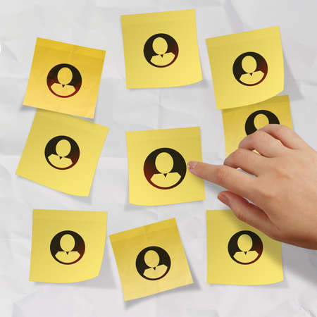 hand pushing sticky note social network icon on crumpled paper background as concept Stock Photo - 22852870