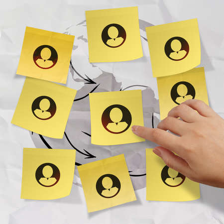 hand pushing sticky note social network icon on crumpled paper background as concept Stock Photo - 22852872
