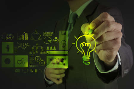 intelligent solutions: businessman hand draws lightbulb with new computer interface as solution business concept