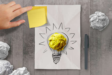 sticky note with another idea light bulb on crumpled paper as creative concept 版權商用圖片