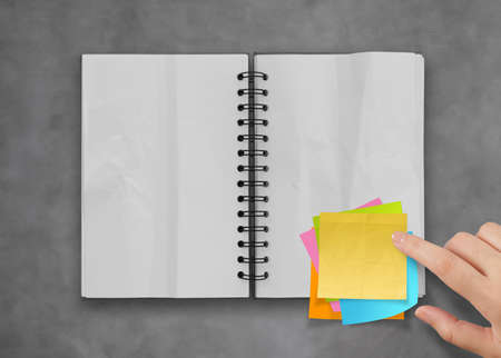 sticky notes with open blank note book on desk top texture Stock Photo - 23401595