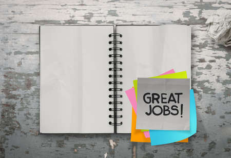 great job: great job word sticky notes with open blank note book on desk top texture