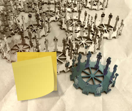 sticky note with 3d figures on connected cogs as leadership concept on crumpled paper photo