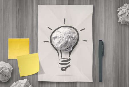 sticky note with another idea light bulb on crumpled paper as creative concept photo