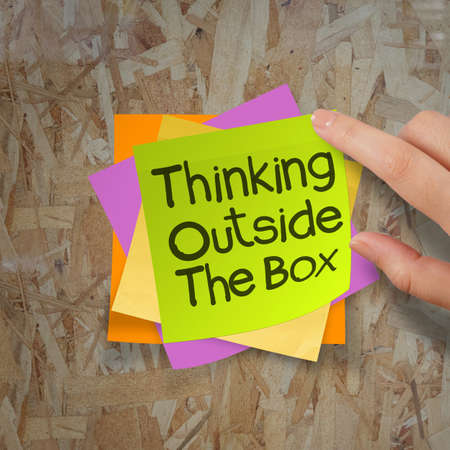 thinking outside the box sticky notes on recycle wood desk top as concept photo