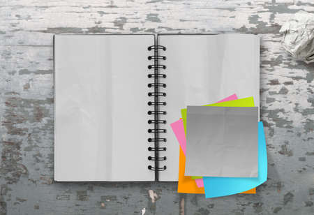 sticky notes with open blank note book on desk top texture photo