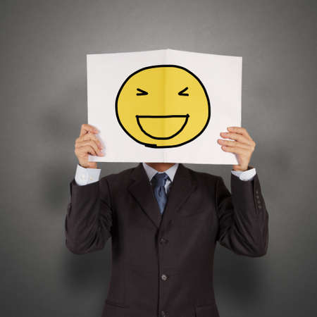 gaily: businessman with the painted happy smile on white book over his face as concept