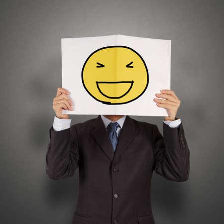 Geschäftsmann mit dem gemalten glückliches Lächeln auf weiße Buch über sein Gesicht als Konzept Standard-Bild