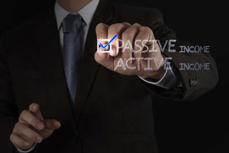 passive earnings: businessman hand checking  passive or acctive income as money concept