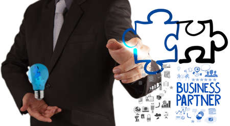 synergism: businessman hand drawing Partnership Puzzle Concept  Stock Photo