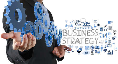 business strategy: businessman hand show gear cogs and  business strategy as concept