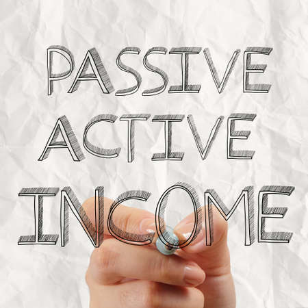 close up of hand drawing passive or acctive income as concept photo