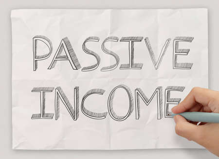 close up of hand drawing passive income on crumpled paper background as concept photo