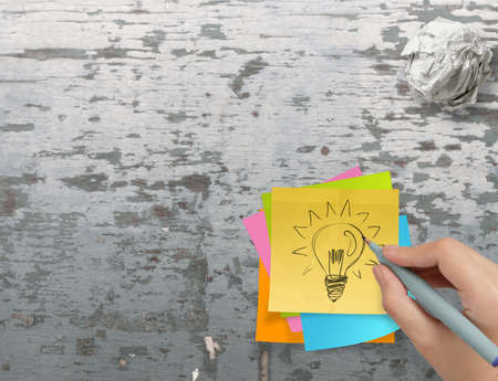 lightbulb as creative on crumpled sticky note paper on texture desk as concept photo