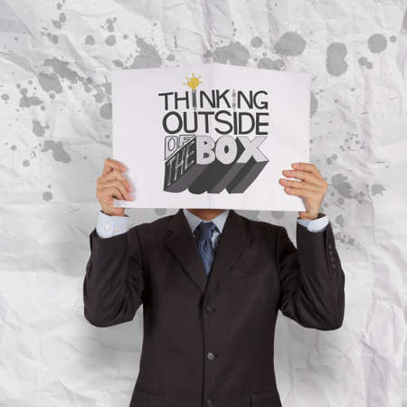 thumbnail: businessman hand showing book of design word THINKING OUTSIDE OF THE BOX as concept Stock Photo