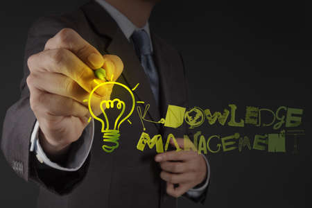 insights: businessman hand drawing  light bulb with design word KNOWLEDGE MANAGEMENT on virtual screen computer as concept Stock Photo