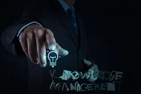 businessman hand pointing  light bulb with design word KNOWLEDGE MANAGEMENT on virtual screen computer as concept