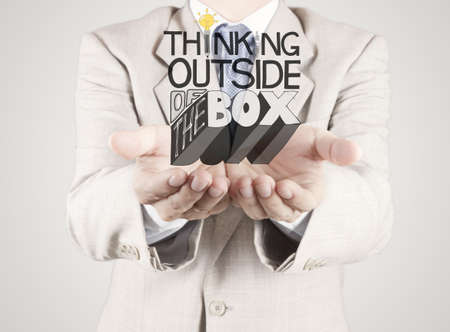 businessman hand showing design word THINKING OUTSIDE OF THE BOX as concept photo