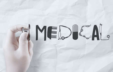hand hold stethoscope showing MEDICAL design word  on crumpled paper background photo