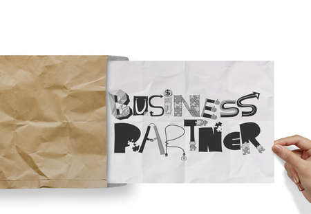 hand pulling crumpled paper from envelope with design word BUSINESS PARTNER as concept photo