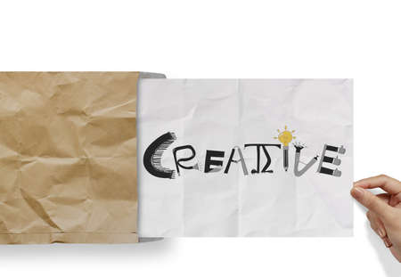 hand pulling crumpled paper from envelope with design word  CREATIVE  as concept photo