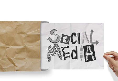hand pulling crumpled paper from envelope with design word SOCIAL MEDIA  as concept photo