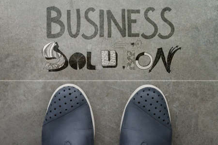 Handdrawn BUSINESS SOLUTION design word on front of business man feet as concept photo
