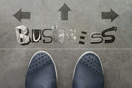 Hand drawn BUSINESS  design word on front of business man feet as concept photo