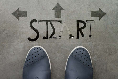 a pair of feet on cement floor print of design word START for the concept of starting point.