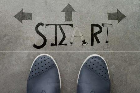 empezar: un par de pies en la impresión del piso de cemento de la palabra del diseño de inicio para el concepto de punto de partida.