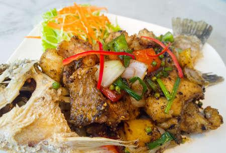 pepe nero: speziato branzino fritto con pepe nero sul piatto bianco