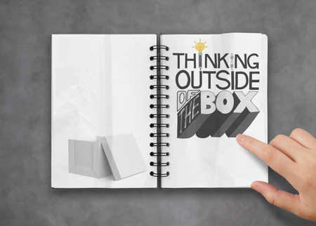 businessman hand showing design word THINKING OUTSIDE OF THE BOX on note book as concept photo
