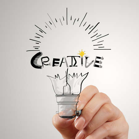 hannd drawing light bulb and CREATIVE word design as concept Stock Photo