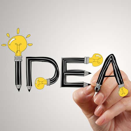 close up of hand writing idea design light bulb as concept