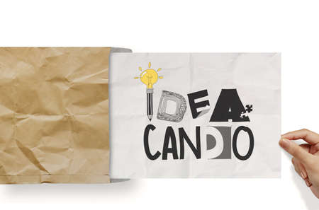 businessman hand show design word IDEA CAN DO on crumpled paper as concept photo