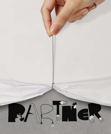 business hand pull rope open wrinkled paper show PARTNER design text as concept photo