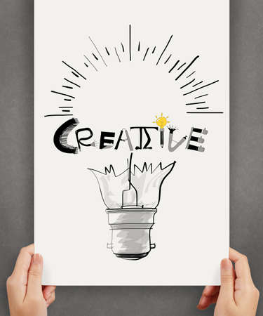 hannd show  light bulb and CREATIVE word design on paper background  as concept photo