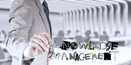 businessman hand drawing design word KNOWLEDGE MANAGEMENT as concept photo