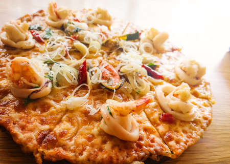 italian cusine:  Seafood spicy pizza on wood table Stock Photo