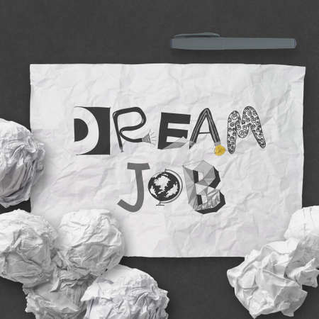 hand drawn design words DREAM JOB on crumpled paper background as concept photo