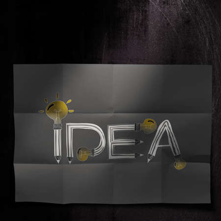 design word IDEA on dark crumpled paper and texture background as concept photo