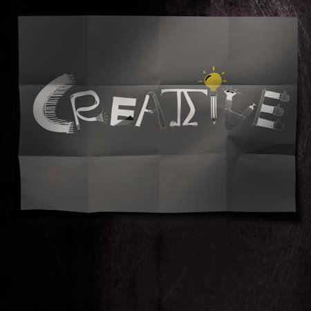 design word CREATIVE on dark crumpled paper and texture background as concept photo