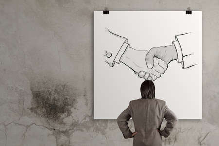 businessman looking hand drawn handshake sign as partnership business concept photo