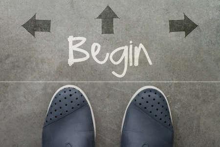 Hand gezeichnet BEGIN Design Wort auf der Vorderseite der Geschäftsmann Füße als Konzept Standard-Bild