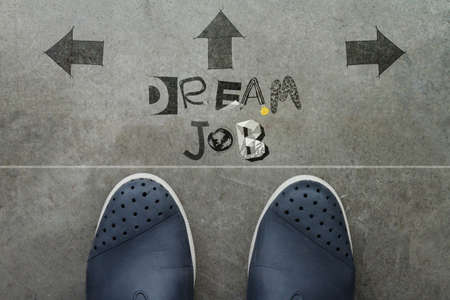 Hand drawn DREAM JOB design word on front of business man feet as concept photo