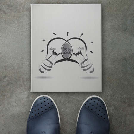 edison: Hand drawn light bulb with BEST IDEA word on canvas board front of business man feet as concept