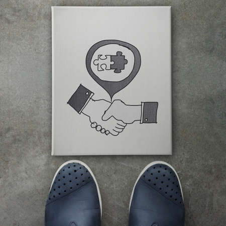 hand drawn handshake signon canvas board on front of business man feet as concept  photo