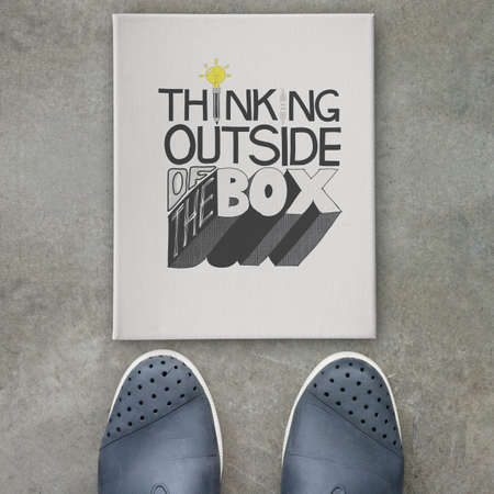 design word THINKING OUTSIDE OF THE BOX  on canvas board on front of business man feet as concept photo