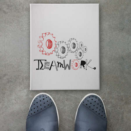 design graphic word TEAMWORK on canvas board on front of business man feet as concept photo
